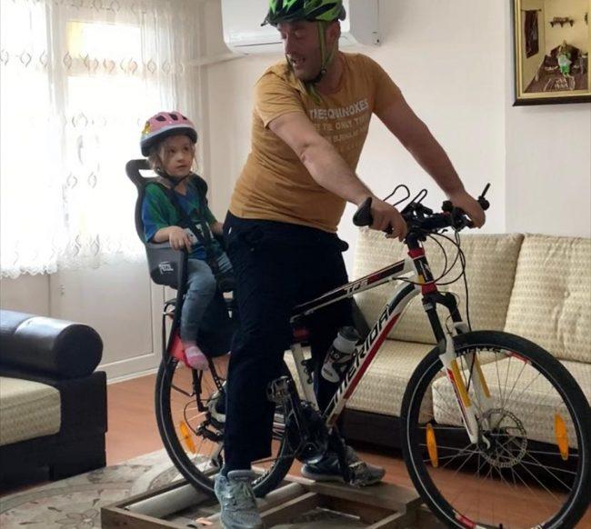 baba ve kızı bisiklet düzeneğini kullanırken görülüyor